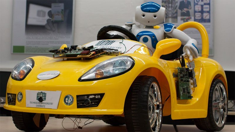 Robot sits in a yellow car.