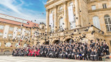 Group photo of the graduates together with the University President in front of the Opera House
