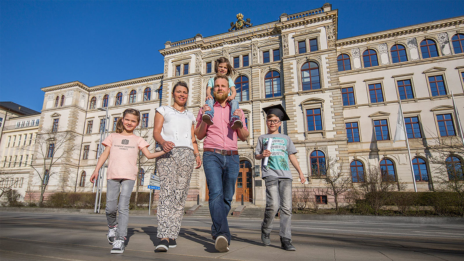 Parents with three chilfrens are walking in front of the university main building.