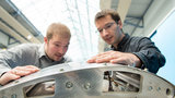 Two young man are looking at a piece of metal.