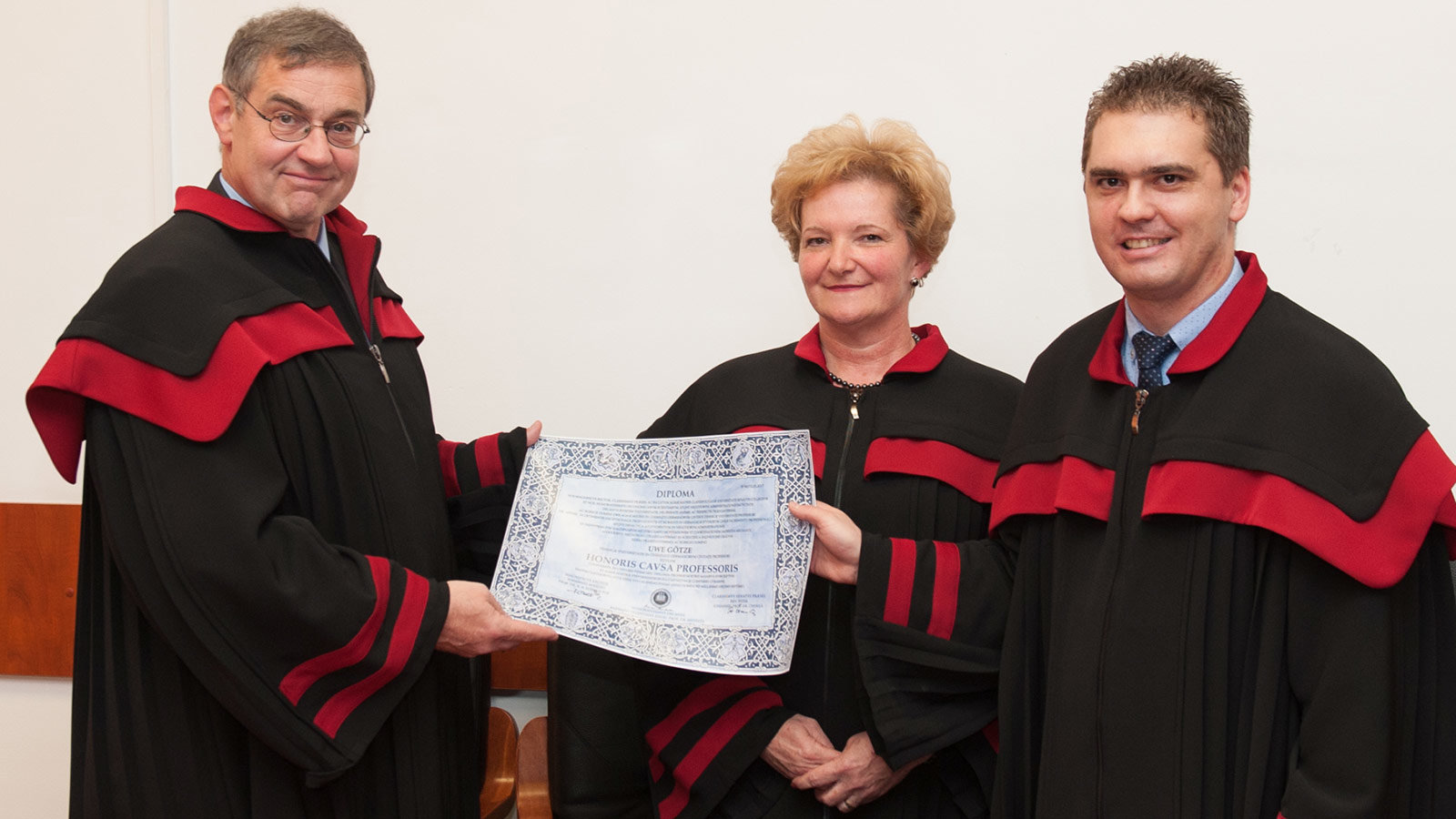 A man gets a certificate from two other persons.