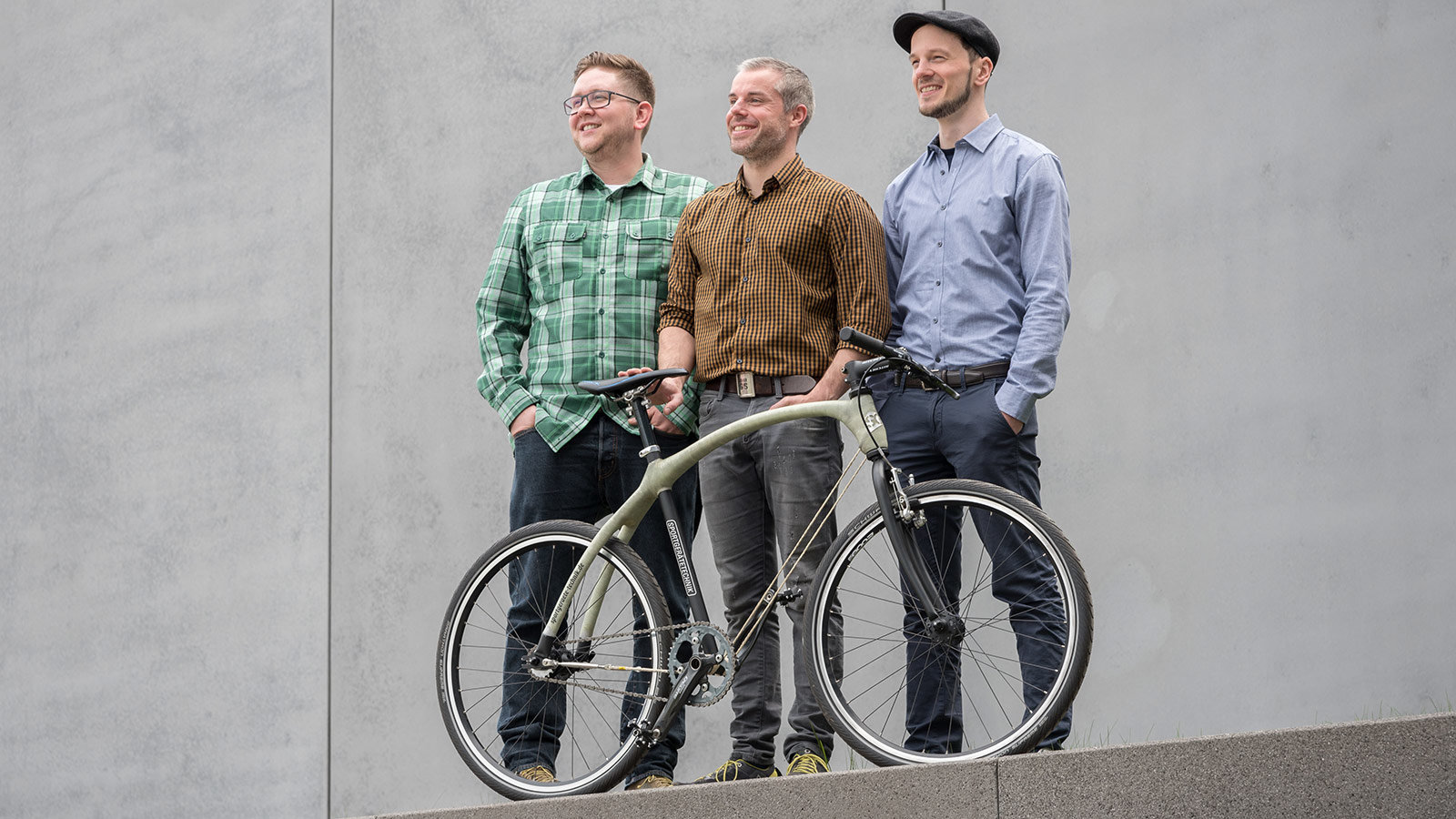 3 men stand behind a bicycle.