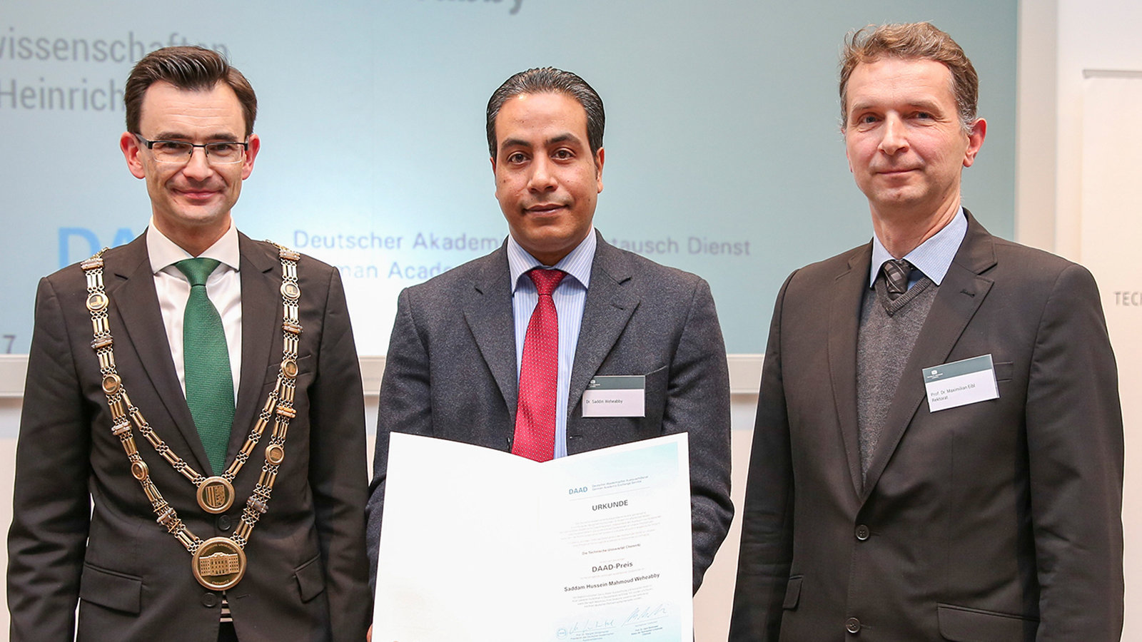 A group of three people, including a person, who is holding a certificate