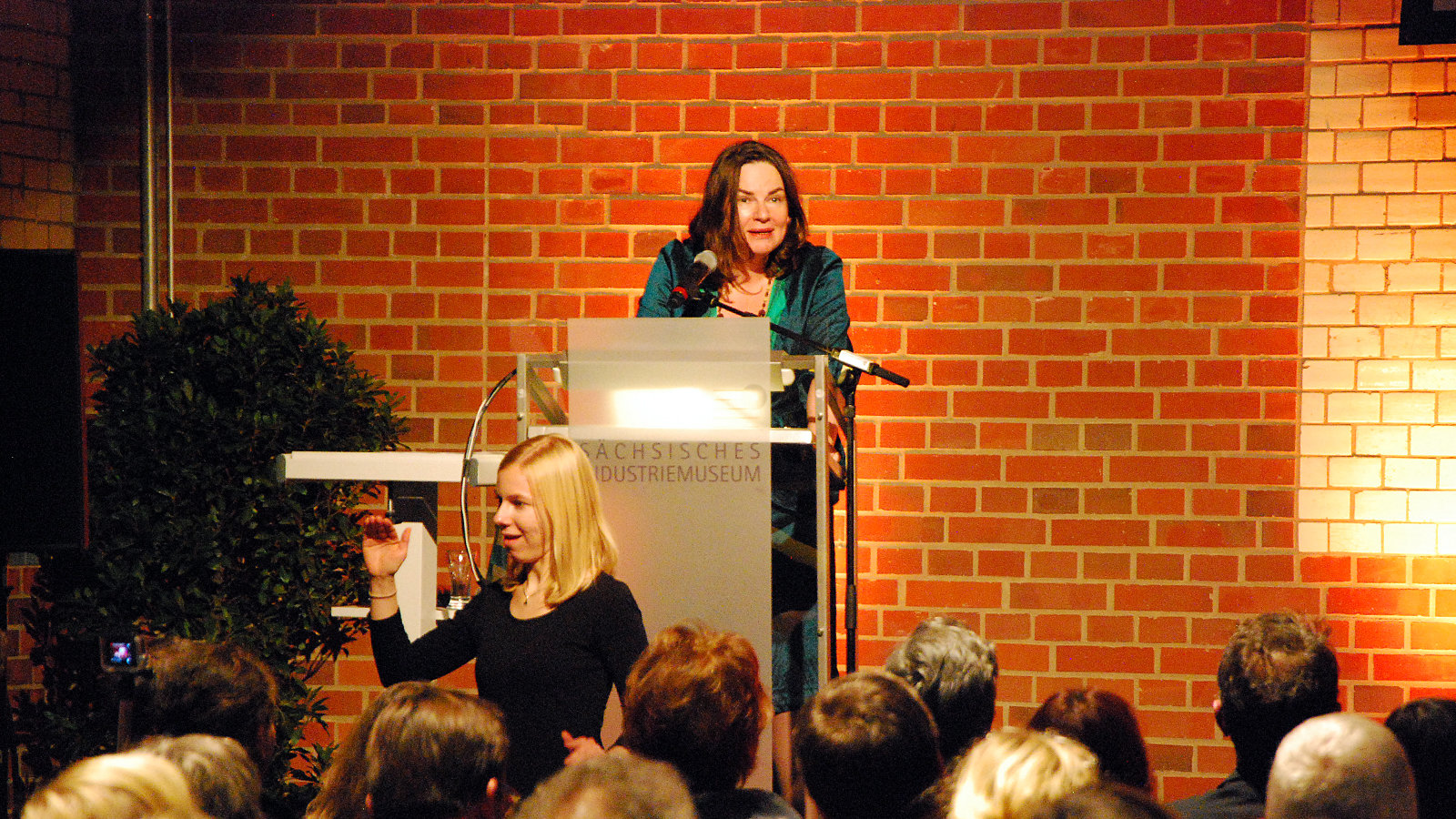 in front of the audience a woman makes gestures, while another woman holds a speech