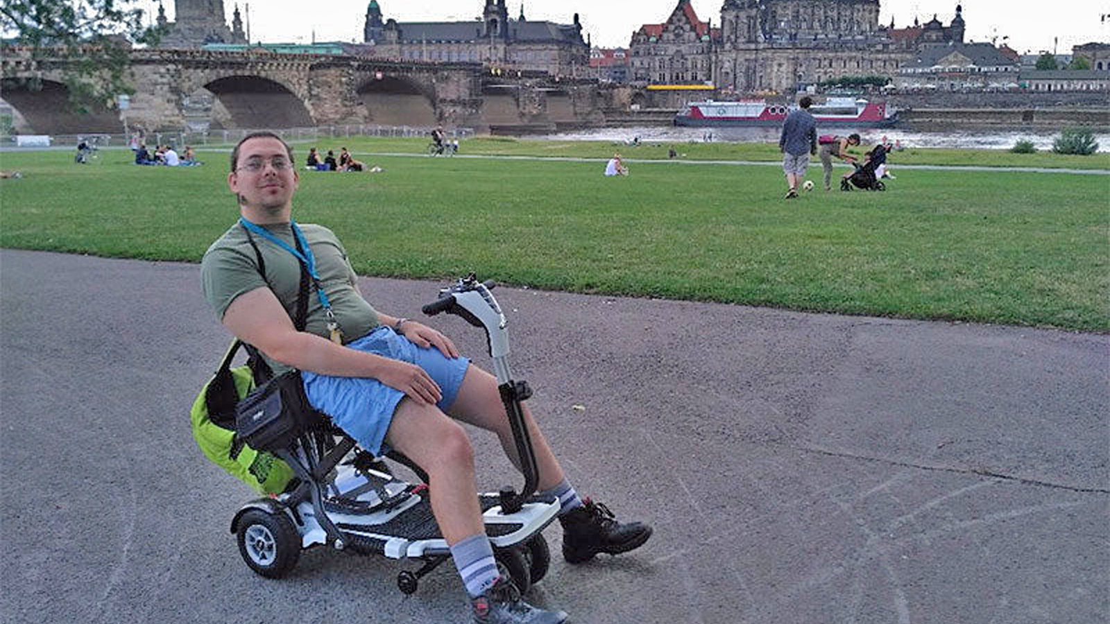 A young man is sitting in a electric scooter