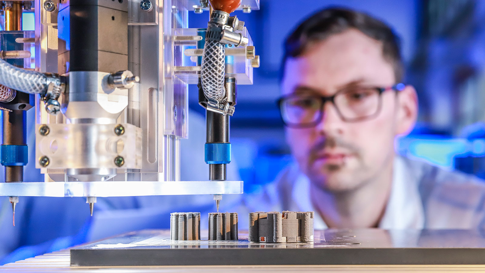 Johannes Rudolph observes the multimedia 3D-printing of an electrical machine in the lab