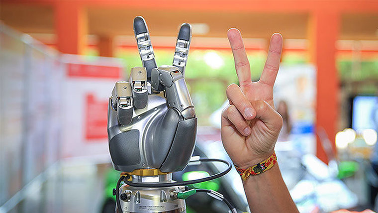 Hands of robot and human shows the victory gesture.