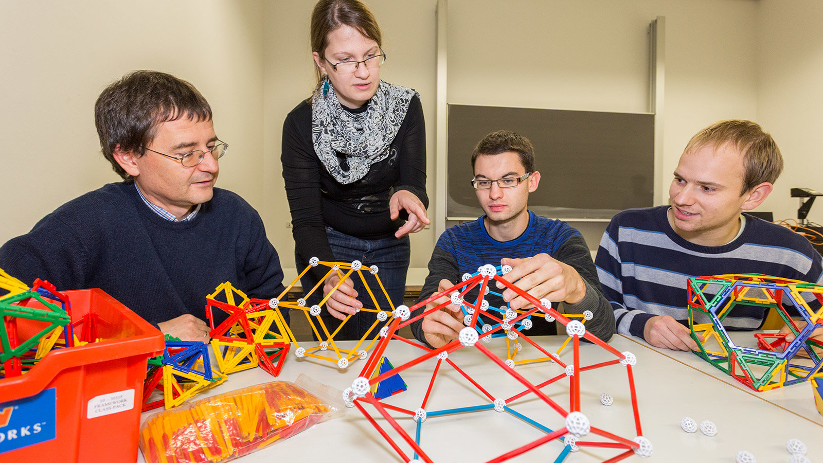 A professor speaks with students about polyhedrons on a table