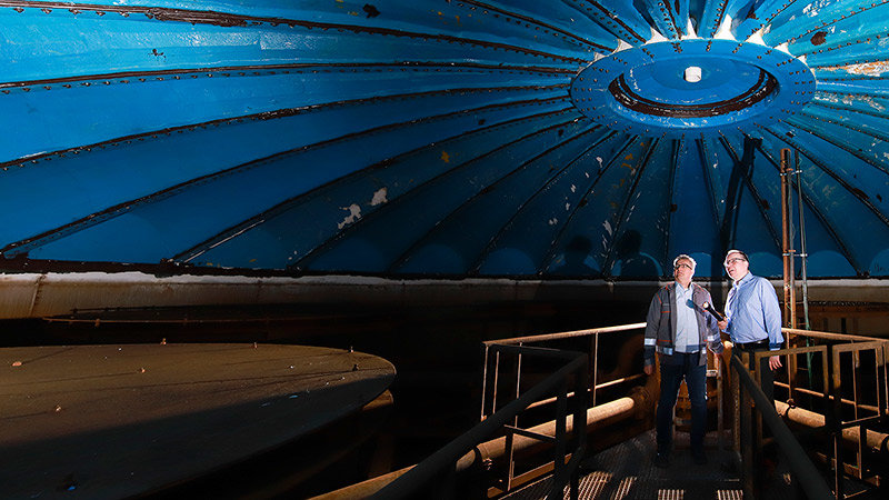 Two men examine the interior of the cold water storage tank.