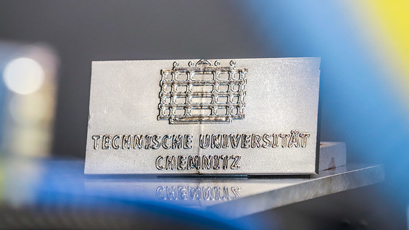 Laser welded Chemnitz University logo shines metallically.