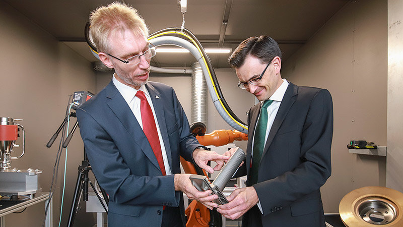 Prof. Lampke and Prof. Strohmeier discuss a small turbine blade that they are holding in their han