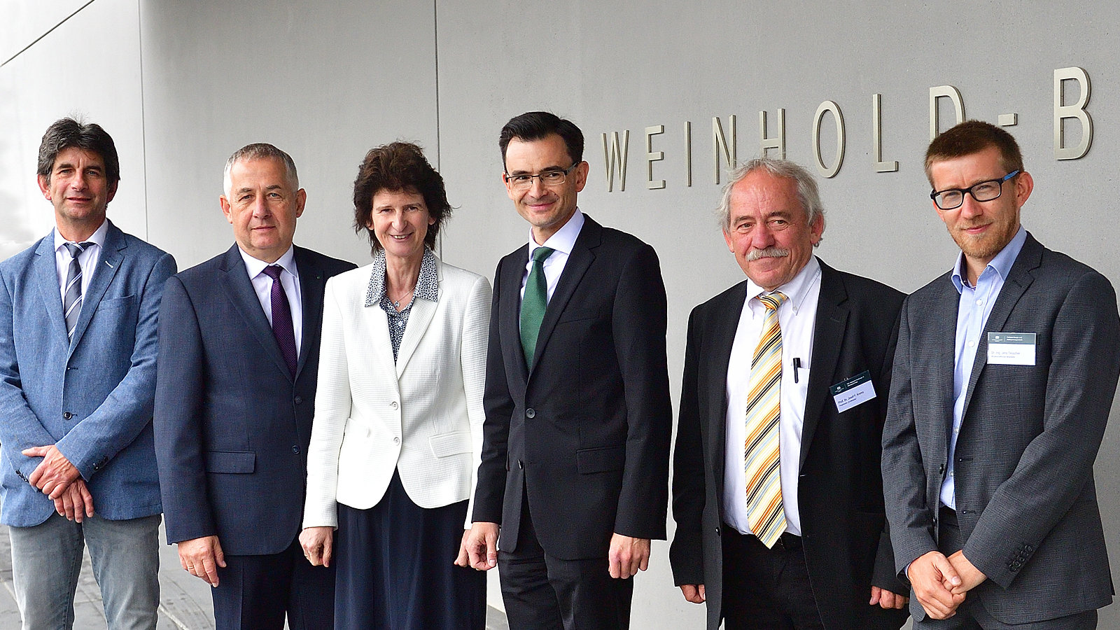 "Five men and one woman in suits stand in front of a building labeled ""Weinhold-Bau""."