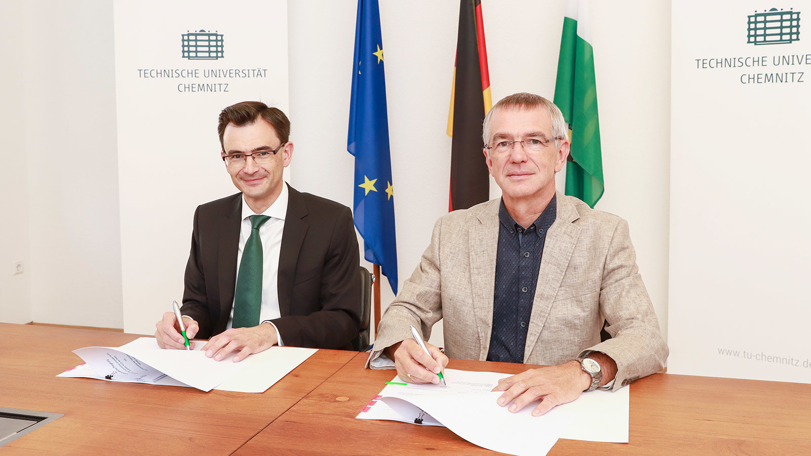 Prof. Dr. Gerd Strohmeier and Dr. Thomas Raschke sitting at a table and signing papers.
