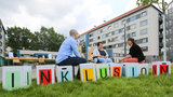 "Three people sitting on cubes with letters that spell ""inclusion""."