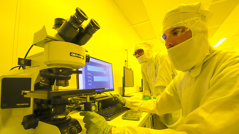 Two researchers work with microscopes in a cleanroom.