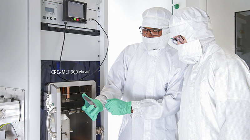 Two researchers examine a coated wafer in a cleanroom.