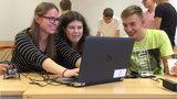 Zwei Schülerinnen und ein Schüler sitzen vor einem Lapzop und lächeln.