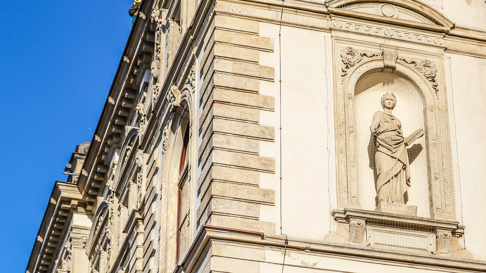 2.25-meter-high statue incorporated into the façade represents scholarship, with a book in a lecturing attitude.
