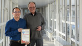 Young asian man and older man are holding a certificate.