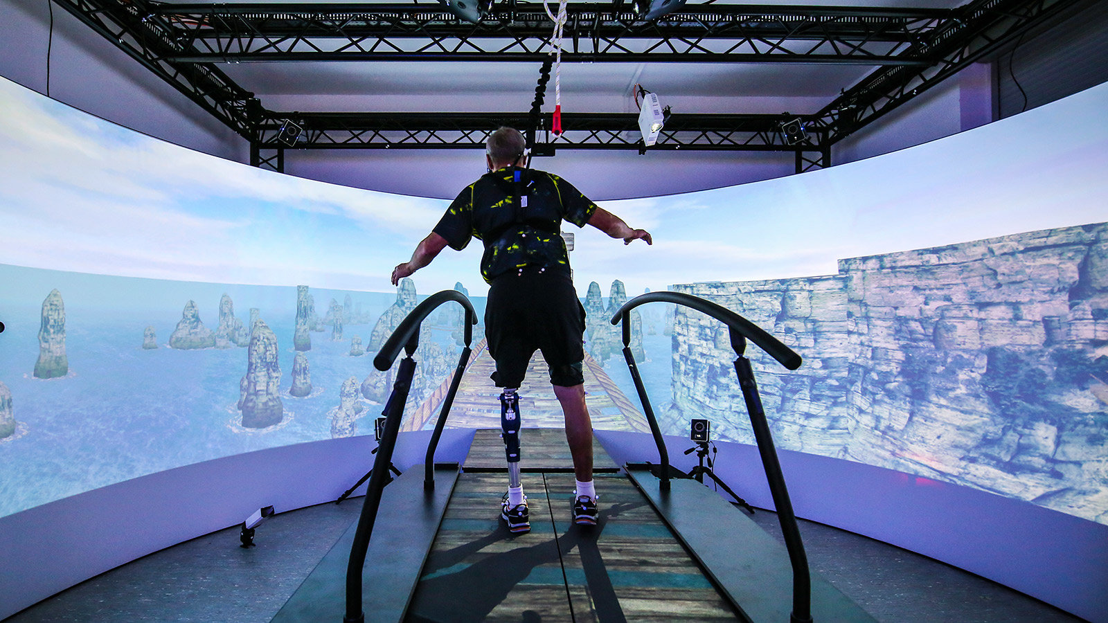 A person stands in front of an VR screen.
