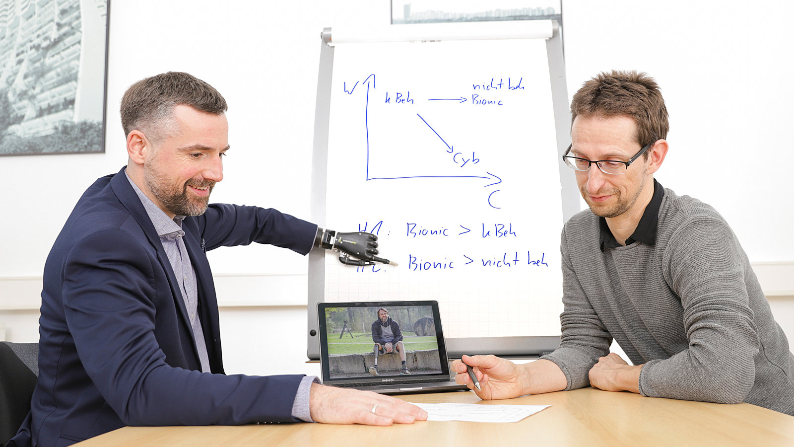 Two men, one with a bionic prosthesis, sitting together. The man with the prosthesis ist pointing at a board with equations.