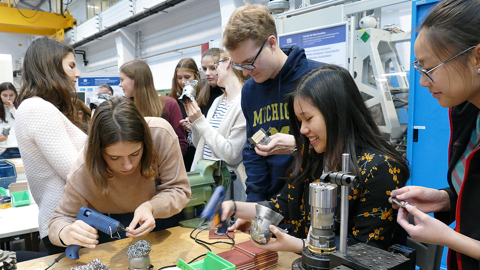 Young people are working on an metallic object.