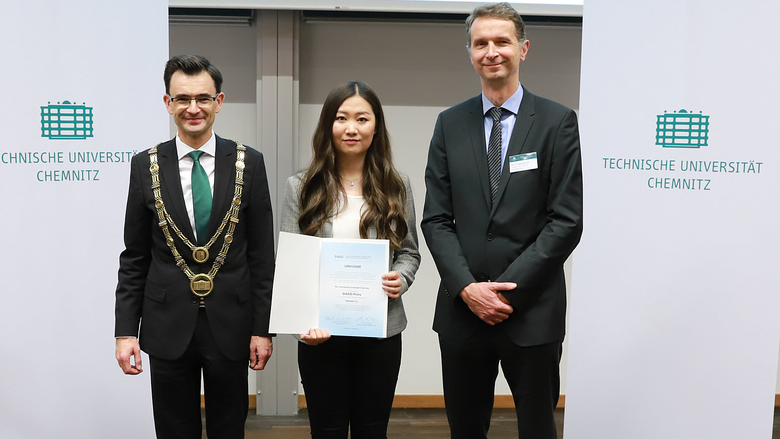 Asian woman stands between two men. She is holding a certificate.