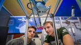 Zwei Männer schauen auf das Modell eines Roboters