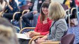 Zwei Frauen unterhalten sich in einem Konferenzraum