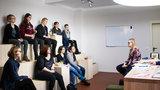 Junge Frau sitzt Schülerinnen und Studentinnen gegenüber.