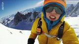 Junger Mann mit Winterjacke, Helm und Sonnenbrille steht vor Berg-Panorama.