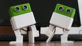 Zwei kleine Roboter tanzen auf einem Tisch