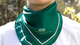 Woman wears a green scarf on her neck.