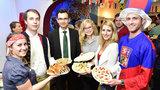 Mehrere Personen stehen nebeneinander und halten Teller mit verschiedenen Speisen in der Hand