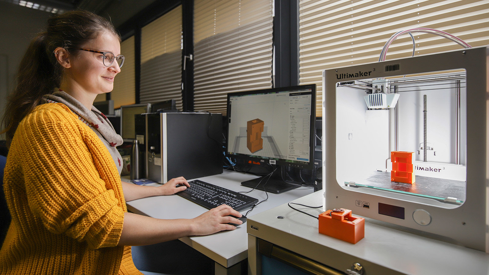 A young woman is working with a 3D printer.