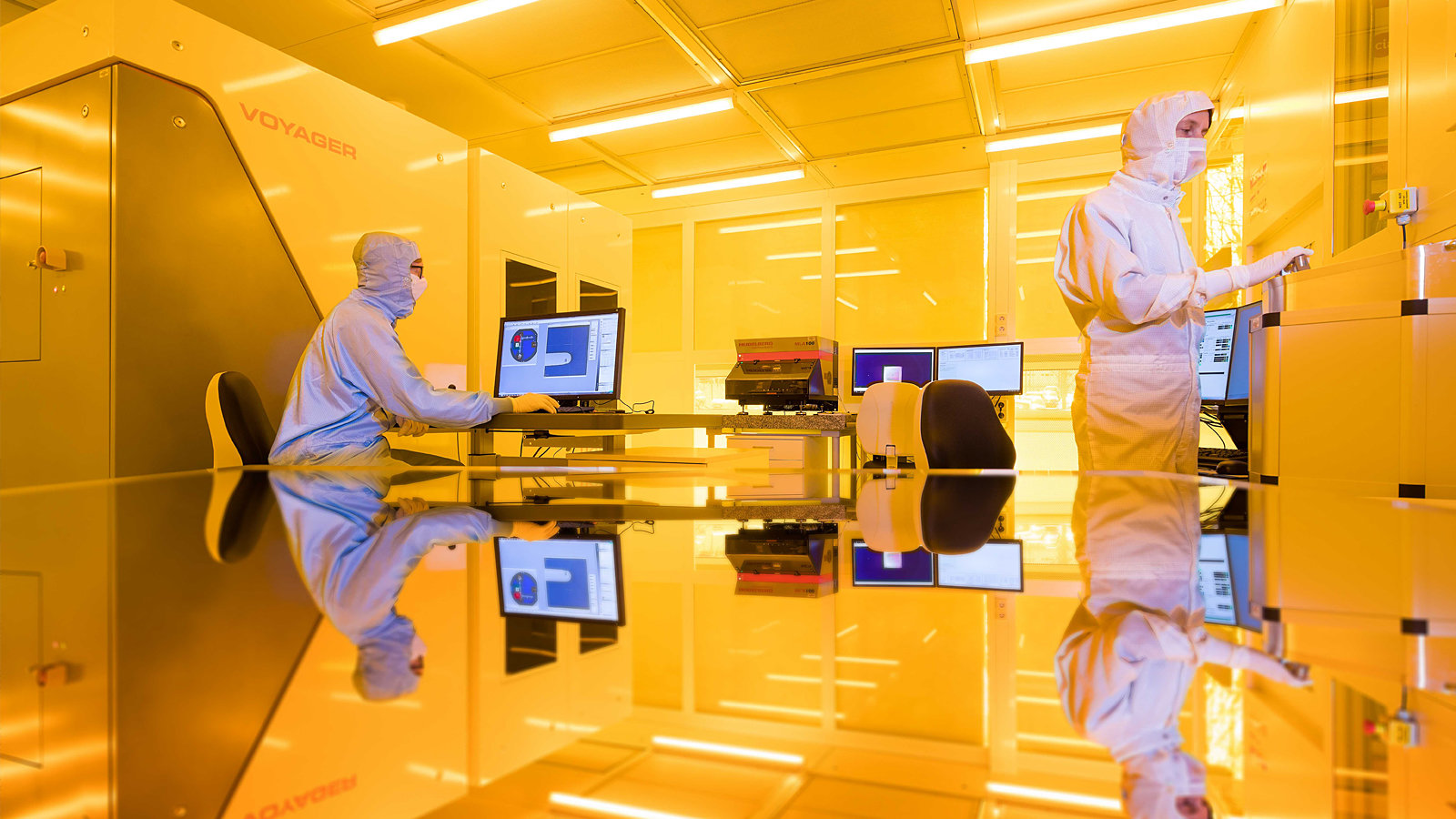Two men in protective suits work in a lab.