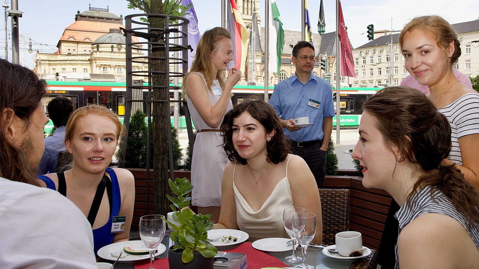 5 young woman talking to each other. The Chemnitz Opera house is in the background.