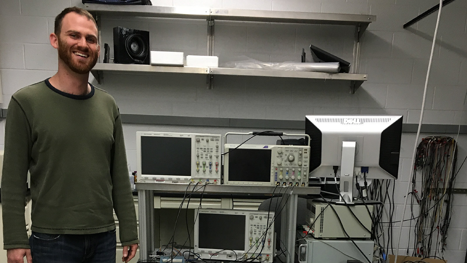 A man standing next to a experimental setup with a lot of cables and platines.