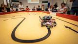 Kleine Roboter fahren über einen Tisch, junge Leute schauen am Rand zu