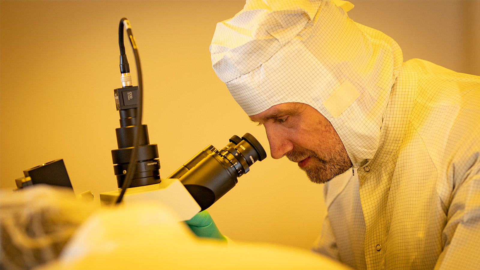 A man in the middle ages wears a protection suite and looks into a microscope.