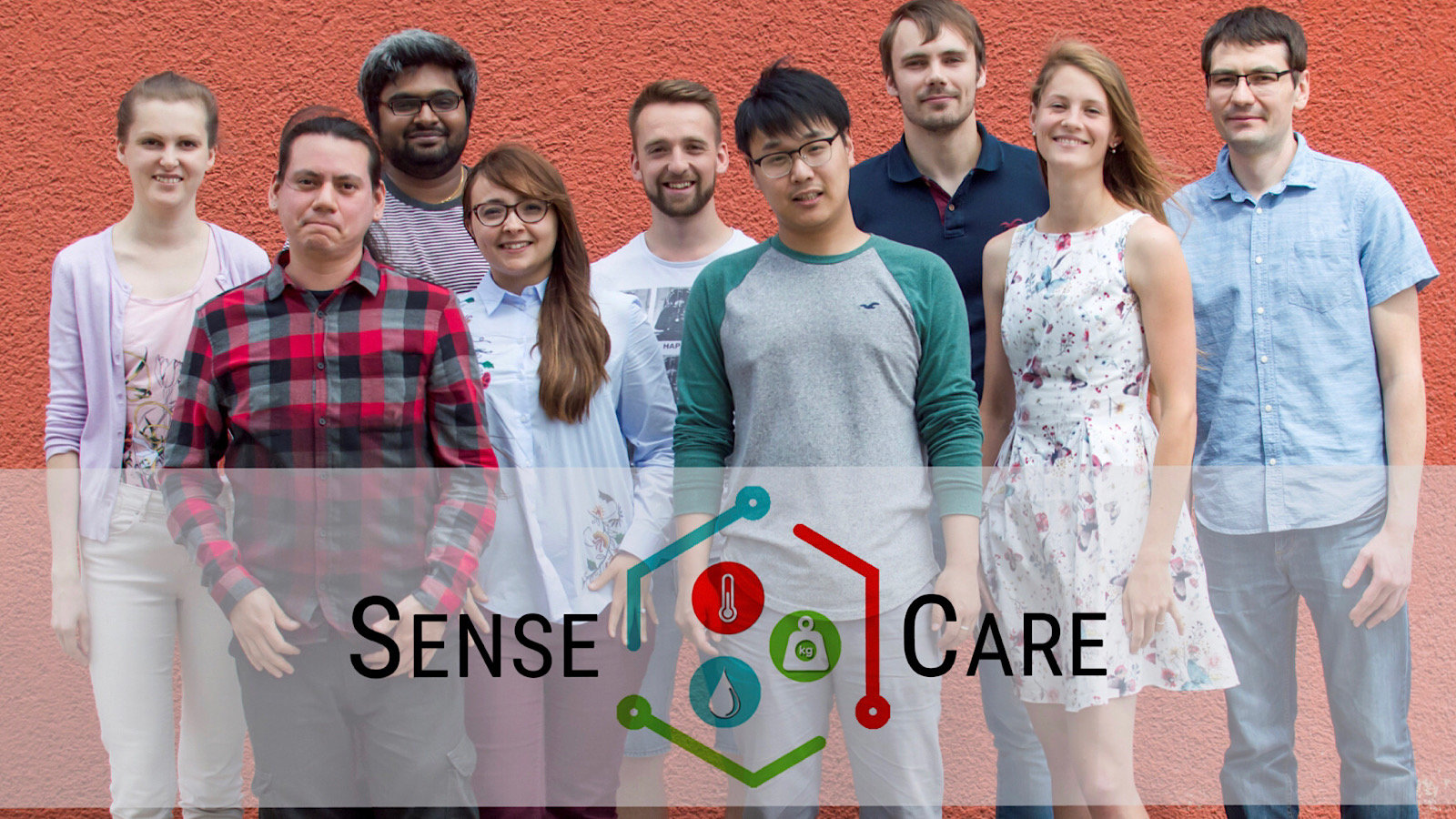 Nine people stand in front of a wall with the SenseCare logo at the bottom of the image