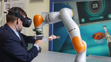 A man wearing a suit and VR goggles holds a drill with help from a robot.