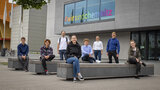 A group of eight people sit spread out among benches in front of the Weinholdbau at Chemnitz University of Technology