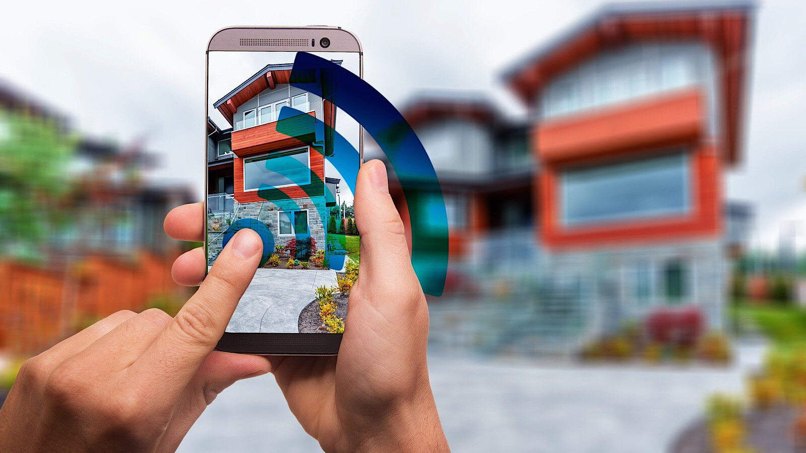 Two hands hold a smart phone, which is taking a photo of a house.