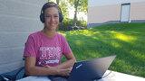 Frau hat Kopfhörer auf und sitzt im Freien an einem Tisch vor einem Laptop.
