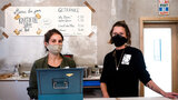 Two young women in masks stand in a restaurant kitchen.
