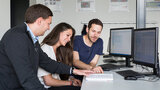 Zwei Männer und eine Frau sitzen vor einem Computer und sprechen miteinander.