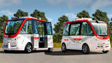 Two small self-driving shuttles sit in a parking lot.