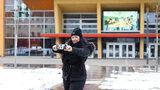 Junge Frau macht mit dem Handy ein Selfie vor einem Gebäude