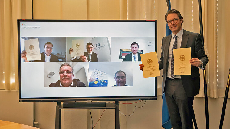 Photo of a man holding up two documents while standing in front of a screen showing a video conference.